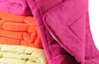 Forskellige farvede tæpper og dyner