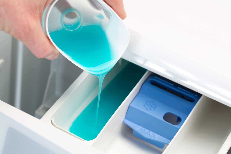 Person, der hælder flydende vaskemiddel i skuffen til vaskemaskinen